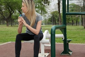 woman in park with asthma inhaler
