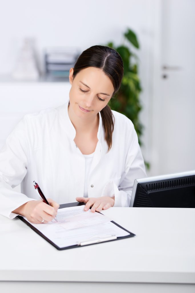 Medical office front desk person filling out form
